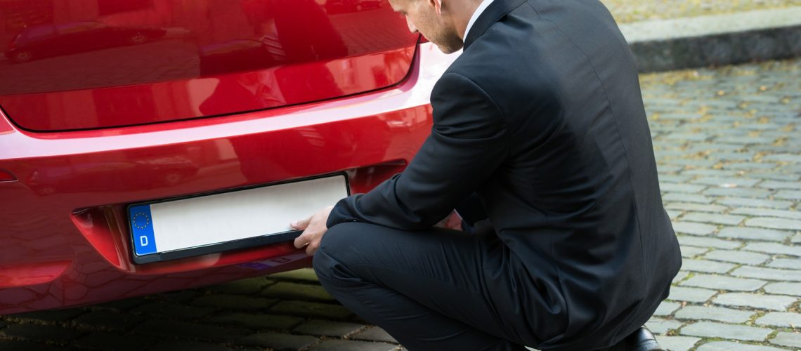 Man Placing New Empty White Number Plate On His Red Car